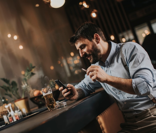 Man drinking beer, smoking cigarette and looking at mobile phone at the pub