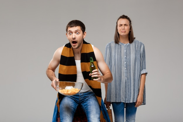 Man drinking beer, watching football, upset woman standing behind, crying