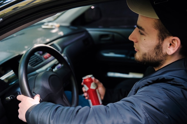 Man drinking beer while driving car