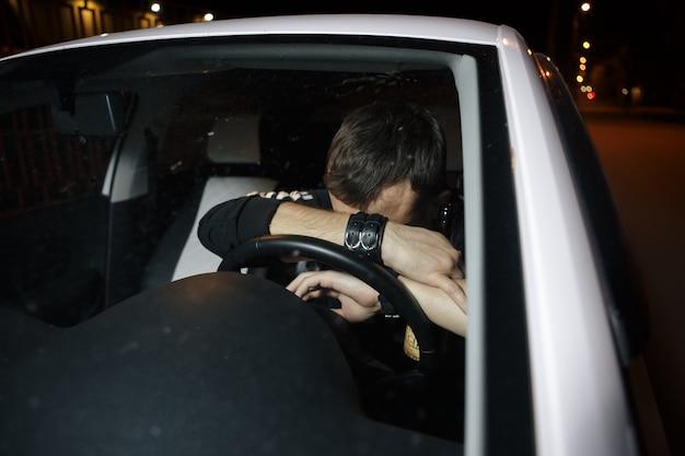 車を運転しながらビールを飲む男性