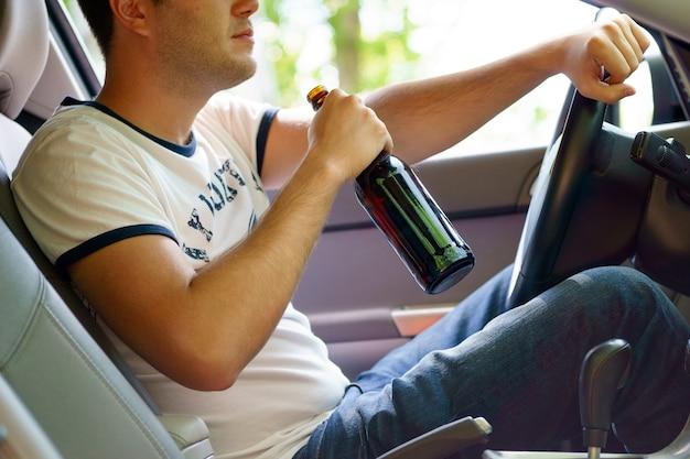 차를 운전하면서 맥주를 마시는 남자.