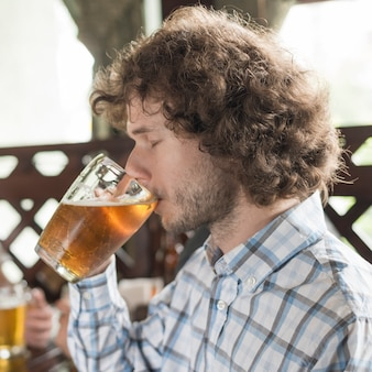 Man drinking beer with closed eyes