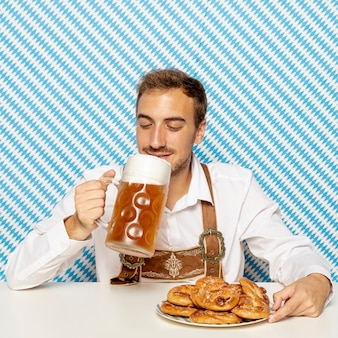 Man drinking blonde beer with patterned background