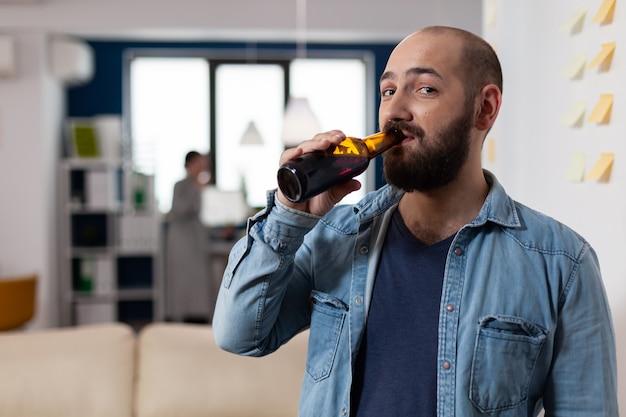楽しみのために同僚との仕事の会議の後にビールのボトルを飲む男