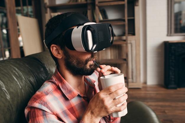Человек пьет коктейль при использовании очков vr дома.