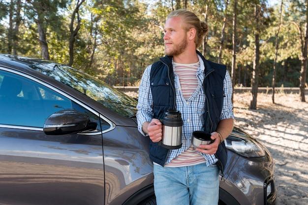 Мужчина пьет кофе и смотрит в сторону