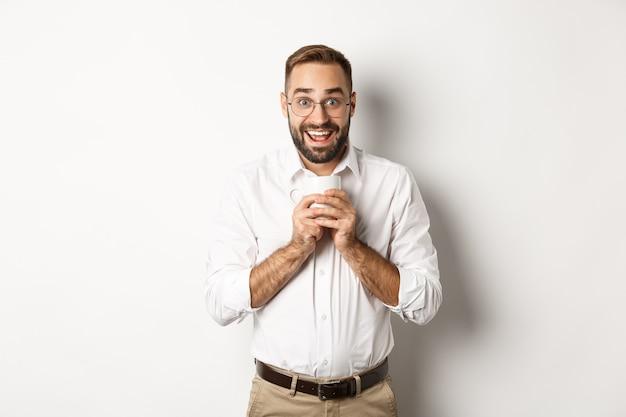 コーヒーを飲み、興奮して、飲み物を楽しんで、白い背景の上に立っている男。