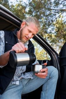 Мужчина пьет кофе и сидит рядом с машиной