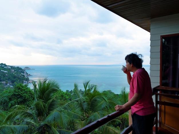 태국 수라타니 코타오 섬에서 아침에 일어난 후 섬의 바다 전망을 감상할 수 있는 객실 테라스에서 커피를 마시는 남자