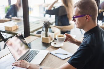 Man drinking coffee at wooden table with laptop