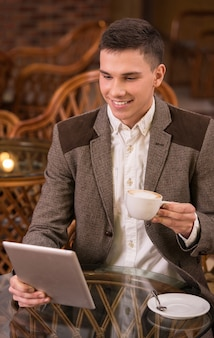 Man drinking coffee in cafe and using tablet computer.