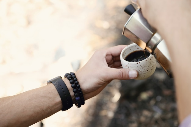 Man drinking coffee in forest