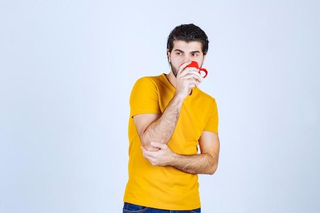 Uomo che beve caffè dalla sua tazza rossa.
