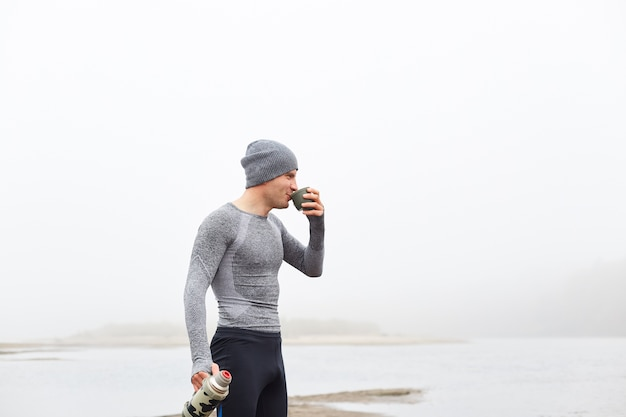 秋の朝に霧の川の近くの魔法瓶カップからコーヒーを飲む男