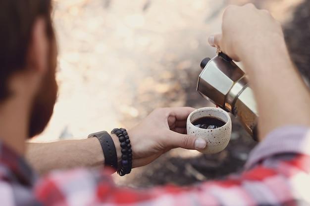 숲에서 커피를 마시는 남자