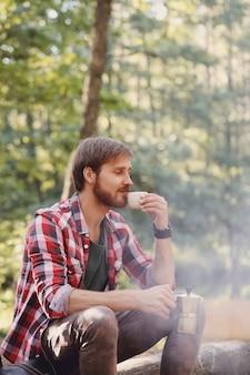 Человек пьет кофе в лесу