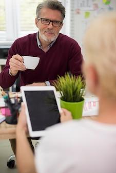 Uomo che beve caffè e ascolta la sua segretaria