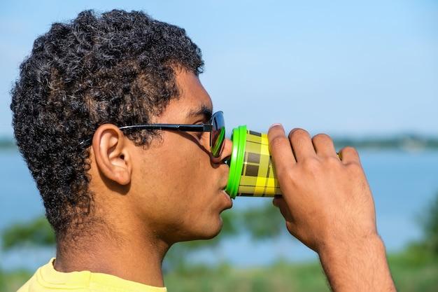 여름에 강 근처에서 야외에서 커피를 마시는 남자