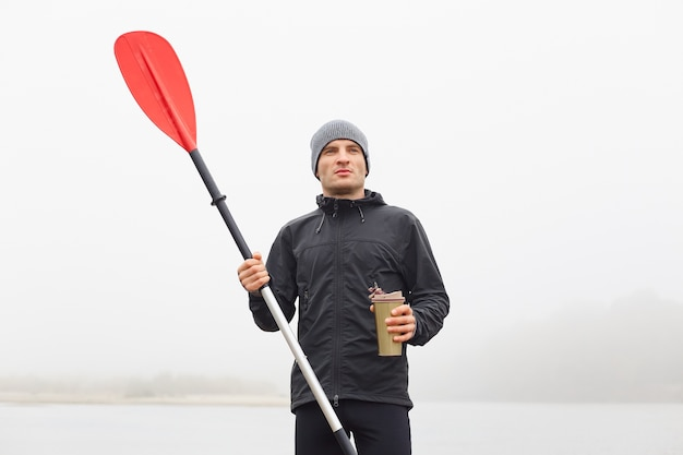 Man drinking coffee outdoors in fall, holding paddle and thermo mug, looking into distance