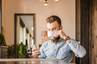 Man drinking coffee while using mobile phone