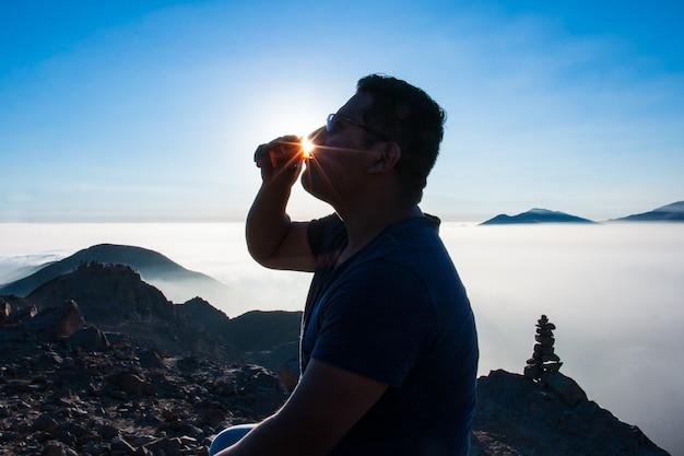 山の夕暮れの美しい夕日の背景の上の小さなガラスから飲む男