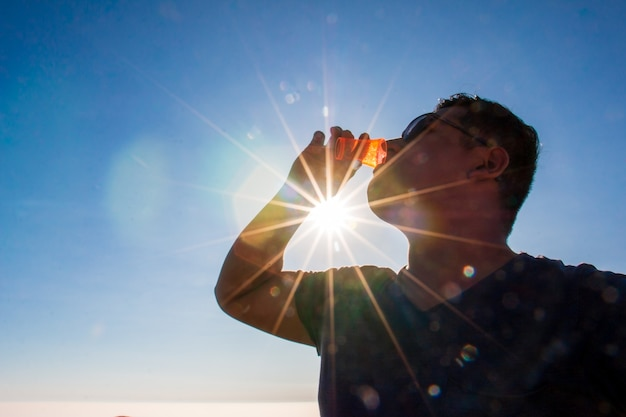 Man drinking from a small glass sun rays and clouds