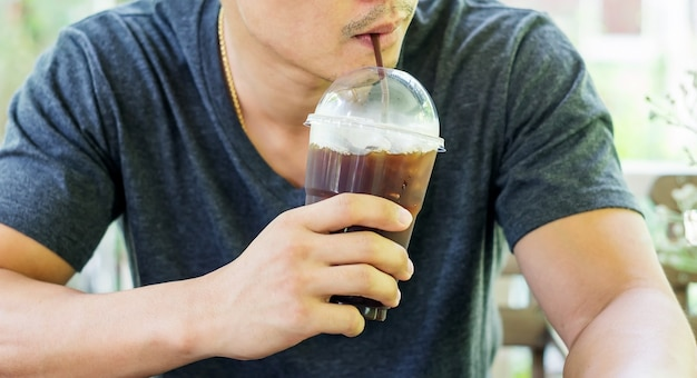 Man drinking an iced coffee in a coffee shop.
