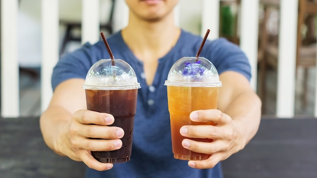 Man drinking an iced coffee and iced tea in a cafe.