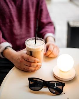 카페에서 여름 테라스에 앉아 라떼 커피를 마시는 남자