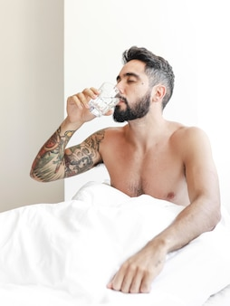 Man drinking water on bed