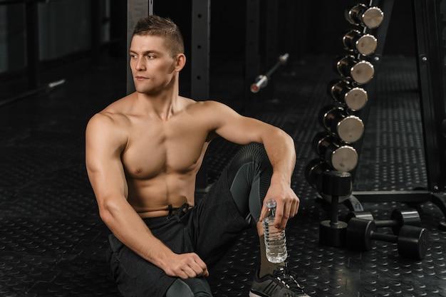 ハードクロスフィットトレーニングの後、ジムで水を飲む男性。 Premium写真