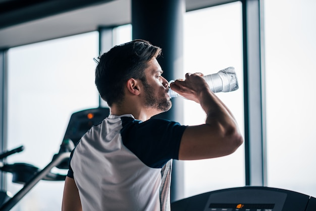 Man drinking water while working out on treadmill in the gym.