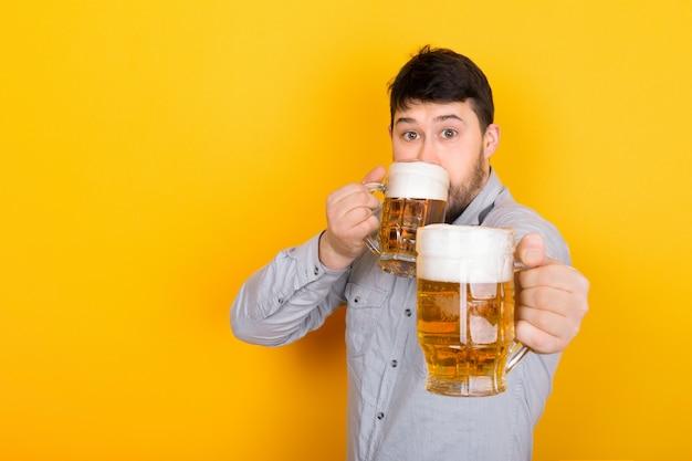 남자는 맥주를 마시고 시청자에게 맥주 한 잔을 제공합니다.