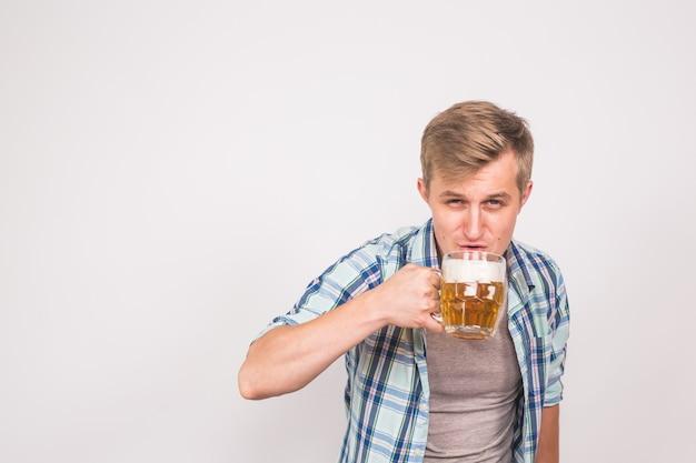 男はビールを飲む。白い背景にラガー パイントを飲むハンサムな若い男。