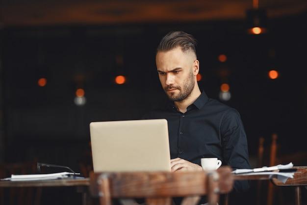 男はコーヒーを飲みます。ビジネスマンはドキュメントを読みます。シャツを着た監督。