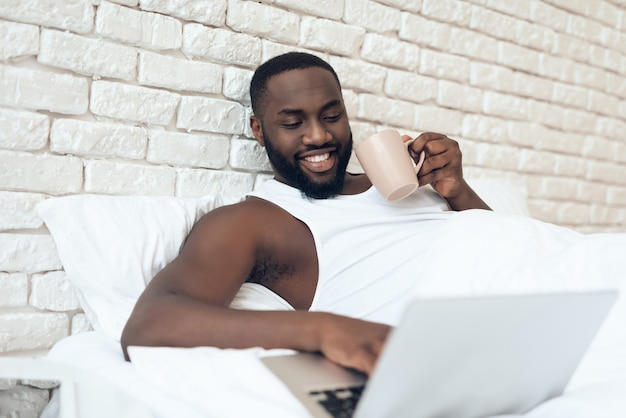Man drinks coffee in bed while working with laptop.