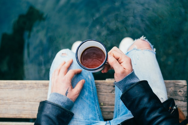 Man drinks coffee from enamel cup outdoors