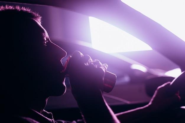 Мужчина пьет кофе из фляги ночного города