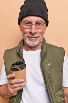 男はテイクアウトカップからコーヒーを飲む帽子カジュアルなtシャツを着て、ベストは余暇を楽しんでいますお気に入りの温かい飲み物を楽しんでいますベージュで隔離された休日を持っています