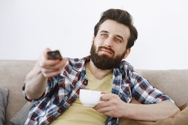 Man drinks coffee. guy watching tv on couch. tv remote control in hands.