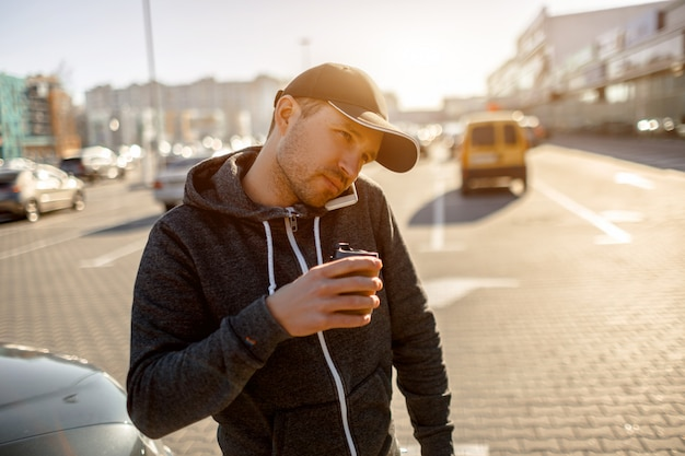 A man drinks coffee in the parking lot of a shopping mall and simultaneously speaks on the phone or smartphone