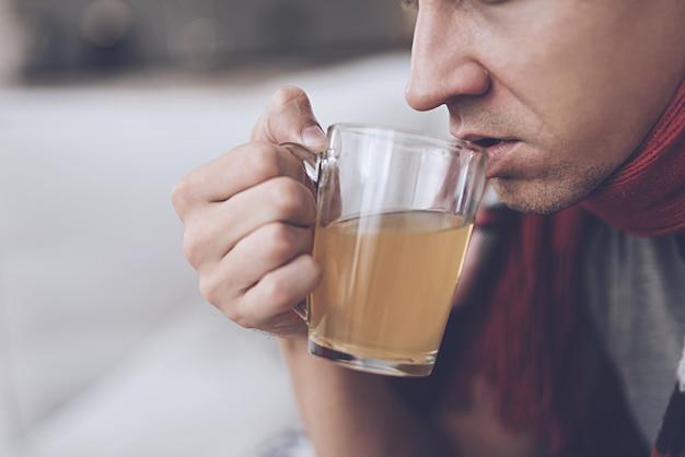 A man drinks orange healing tea from a glass mug