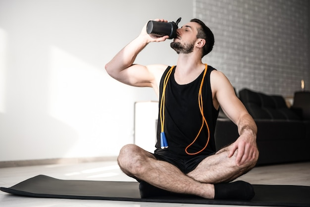 Man drinks water after hard workout and sits with crossing legs. black yoga mat. man is very tired after yoga practice. take care of youself concept. drink more water. smart modern room on background.