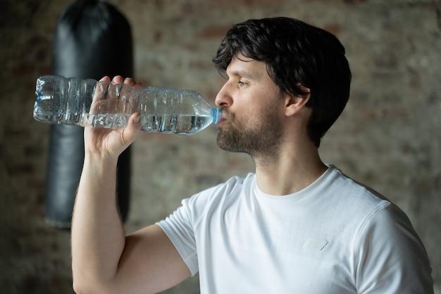 남자는 체육관 건강 관리 및 운동에 병에서 물을 마신다