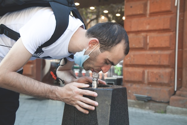 Man drinks water from street fountain.