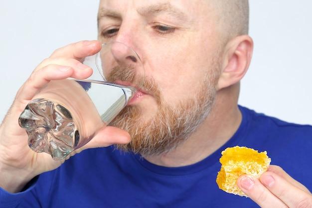 남자는 꿀의 물 시음을 마신다