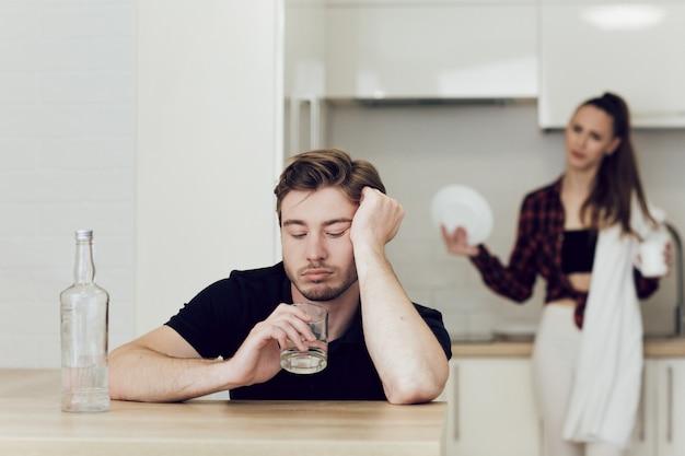 Человек пьет, сидя за столом на кухне