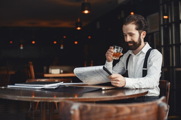 남자는 위스키를 마신다. 사업가 문서를 읽습니다. 셔츠와 멜빵을 입은 감독.
