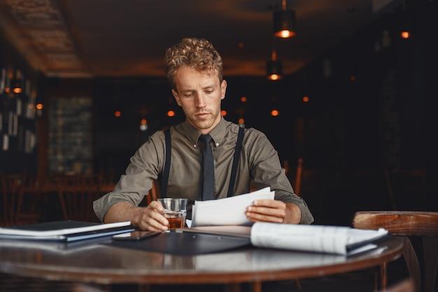 Мужчина пьет виски. бизнесмен читает документы. режиссер в рубашке и подтяжках.