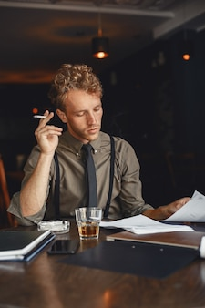 Man drinks whiskey. businessman reads documents. director in a shirt and suspenders.